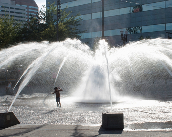 A happy kid running through Portland's Salmon St Fountain's copious spray